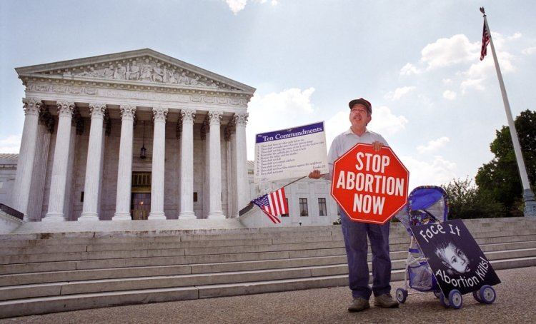 An anti-abortion protester holds a stop sign and the Ten Commandments on the sidewalk in front of the U.S. Supreme Court. /Shutterstock